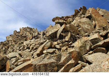 Mountain Peak Of Huge And Small Stones Against The Sky With Clouds In Summer In Sunny Weather. Stone