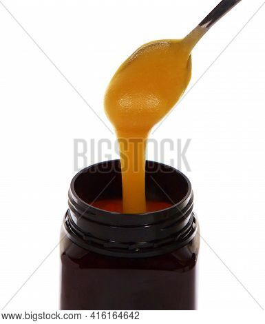 Manuka Honey Drains From A Spoon Isolated On White