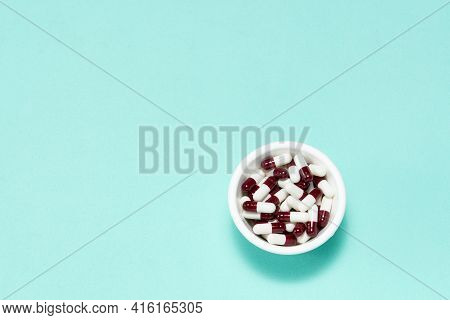 Pharmaceutical Medicine Pill Capsules, In Bowl On Colorful Background.