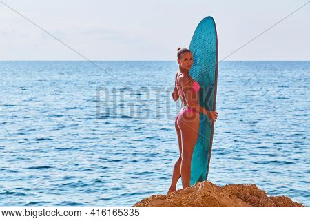 Tanned Girl Posing With Surfboard On Beach. Sea View And Hot Weather. Idea Of Summer Time, Surfing,
