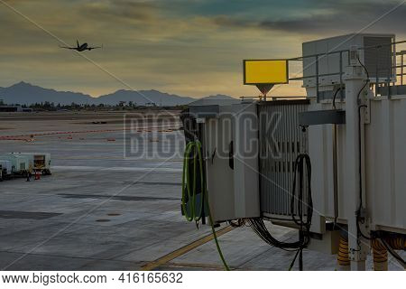Sky Harbor Airport Airport At Sunset With Plane Taking Off On Boarding Bridge Used To Connect Airpor