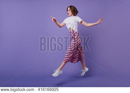 Full-length Shot Of Excited Pretty Girl With Wavy Hairstyle Jumping On Purple Background. Stylish Go