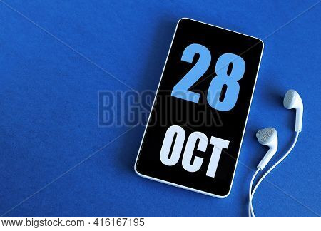 October 28. 28 St Day Of The Month, Calendar Date. Smartphone And White Headphones On A Blue Backgro