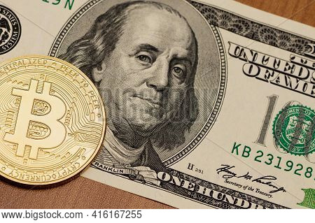 Physical Bitcoin Lies On One Hundred Dollar And One Hundred Euro Bills. Close Up.