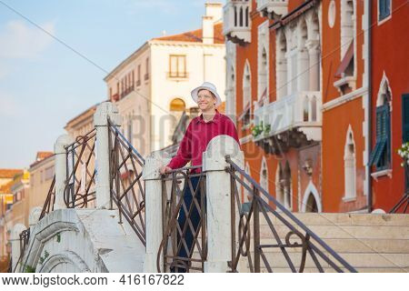 Smiling Male Tourist In Mid Forties With Red Shirt And White Hat Standing On Arched Bridge In Venice