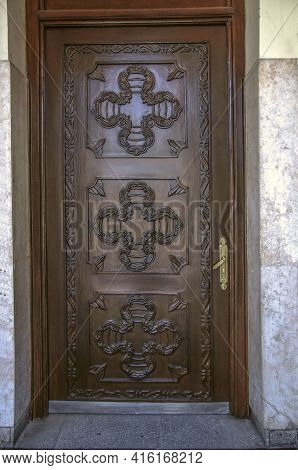 Brown Wooden Door Covered With Carved Decorative Patterns At The Entrance To The Belfry Of St. Sarki
