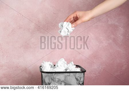 Woman Throwing Crumpled Paper Ball Into Basket On Pink Background, Closeup