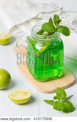 Homemade Lemonade With Tarragon, Lime And Lemon. A Refreshing Cocktail Of Bright Green Color In A Gl