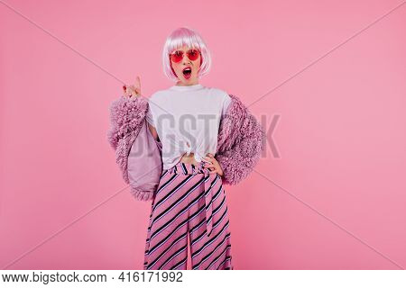 Unpleased Female Model In Trendy Fluffy Jacket Posing In Studio. Attractive Disappointed Girl In Pin