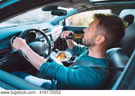 Drunk Driving. Young Man Drinking Beer While Driving A Car. Driver Under Alcohol Influence. Dangerou