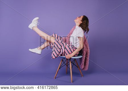 Good-humoured Girl Sitting On Chair And Waving Legs. Studio Shot Of Laughing Brunette Lady In Stylis