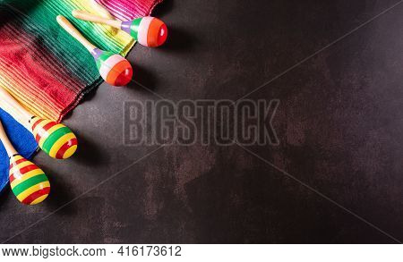 Cinco De Mayo Holiday Background Made From Maracas, Mexican Blanket Stripes Or Poncho Serape On Dark