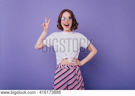 Excited Young Lady In Trendy Summer Clothes Posing With Peace Sign On Purple Background. Good-humour