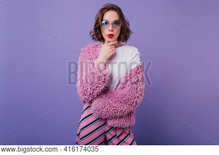 Attractive Caucasian Woman In Bright Attire Looking To Camera With Surprised Face Expression. Indoor