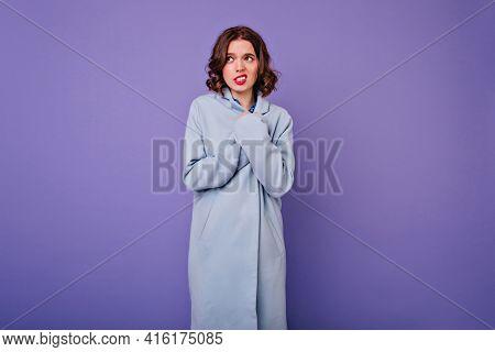 Shy Woman With Short Wavy Hair Posing In Elegant Long Coat. Beautiful European Curly Girl In Blue At