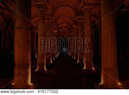 A Dark Colonnade Of An Ancient Chamber With Columns Lit With Red Light
