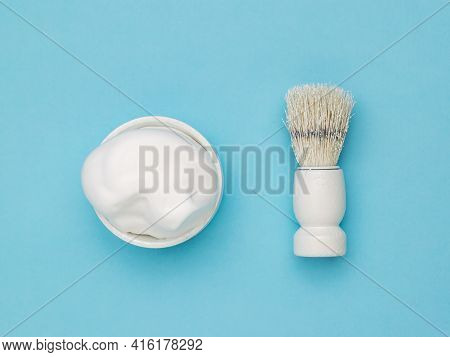 Shaving Foam In A White Bowl And A White Shaving Brush On A Blue Background. Set For Care Of A Man's