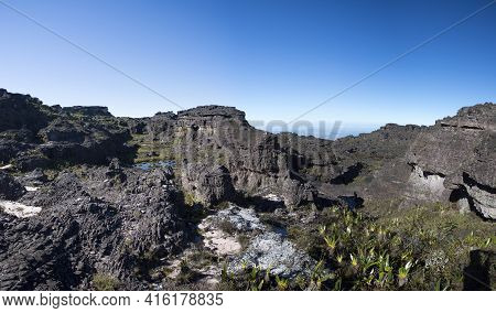 Landscape At The Top Of Mount Roraima In The Morning With Blue Sky. Black Volcanic Stones, And Endem