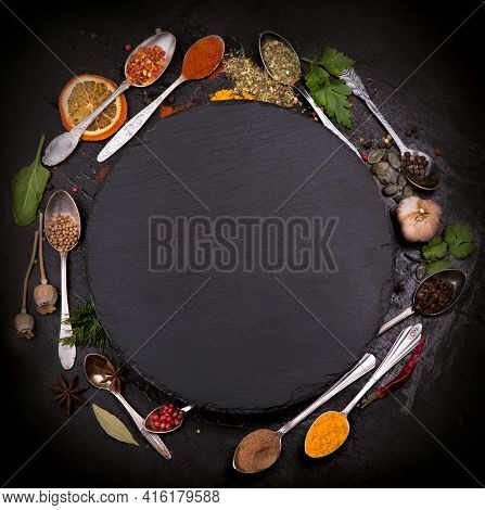 Spices And Condiments For Cooking On A Black Background.