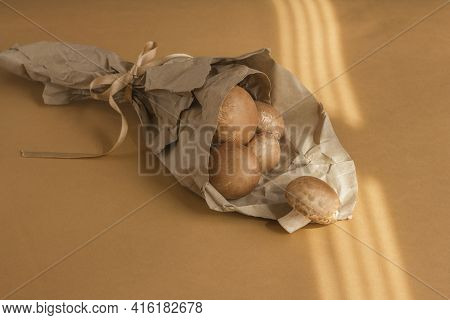 Raw Mushrooms Champignons Packed In A Paper Bag On A Beige Background, Cooking Fresh Champignons.