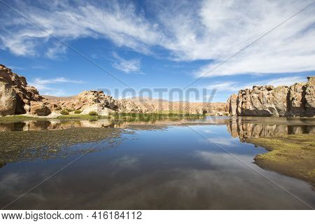 Small Lake With Green Grass And Strange Geological Formations Against A Cloudy Blue Clear Sky In Bol