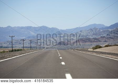 The Famous Ruta 40 (route 40) Paved Road Parallel To The Andes Against A Blue Sky And Going To El Le