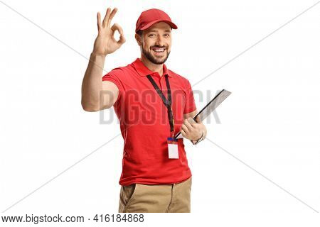 Cheerful male shop assistant gesturing ok sign with hand and holding a document isolated on white background