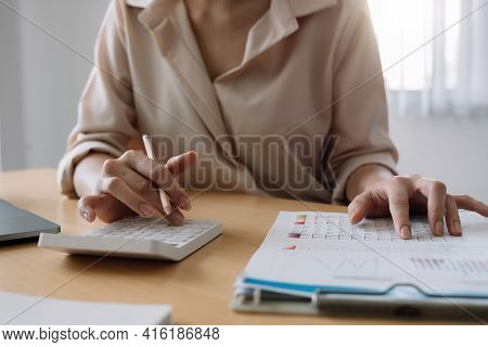 Close Up Of Businesswoman Or Accountant Hand Holding Pencil Working On Calculator To Calculate Finan