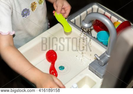 A Child Plays In The Children's Kitchen. Baby Washes Plastic Dishes In The Sink Close-up, Children's