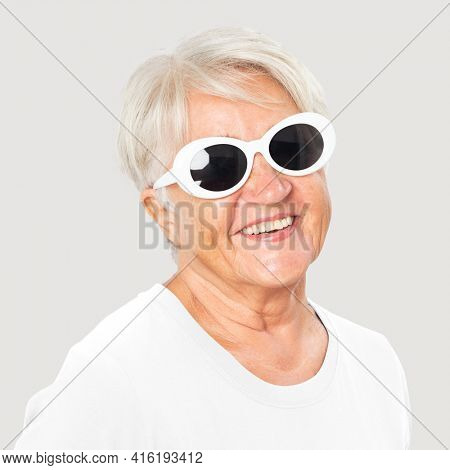 Happy senior woman wearing white oval sunglasses for summer apparel portrait