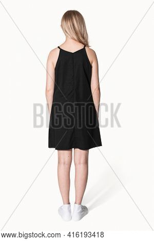 Blonde girl in black a-line dress for teenage summer apparel shoot rear view