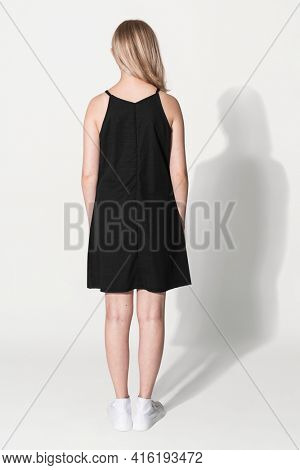 Blonde girl in black a-line dress for youth summer apparel shoot rear view