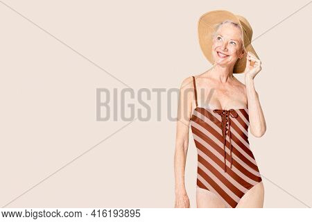 Senior woman in red striped one-piece swimsuit summer apparel with design space