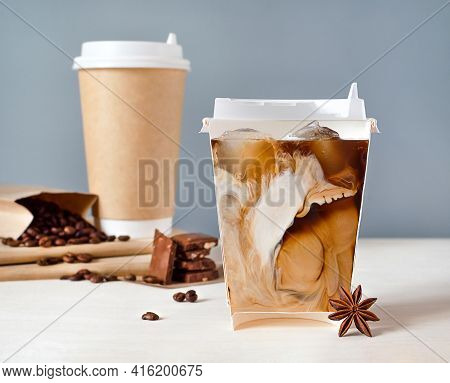 Still Life With Cold Coffee And Milk In A Glass Cut In Half. Coffee Inside The Cup. Unusual View