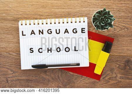 Notebook With Inscription Language School, Pen, Spain Flag, Marker On Wooden Brown Desktop