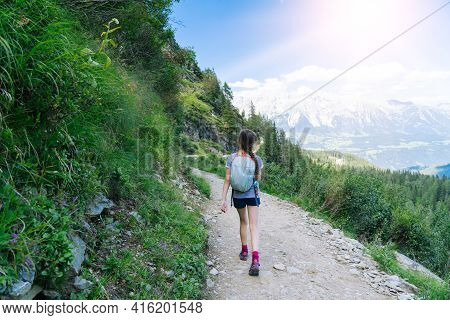 Girl Hiking On Beautiful Summer Day In Alps Mountains Austria, Resting On Rock And Admire Amazing Vi