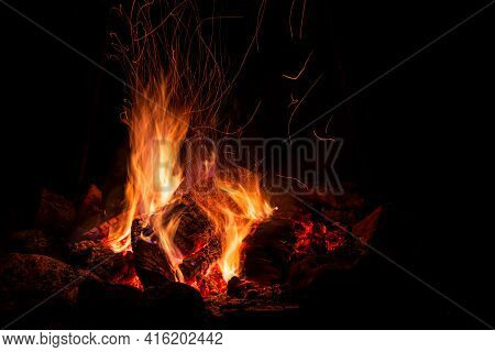 Night Campfire With Available Space. Big Bonfire Against Black Background. Sparks Of Bonfire And Fir