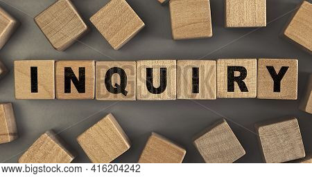 The Word Inquiry On Small Wooden Blocks At The Desk. Conceptual Photo. Top View