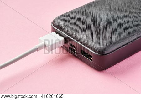 Usb Connector Is Connected To Power Bank On A Pink Background. Charging Gadgets. Close-up, Selective