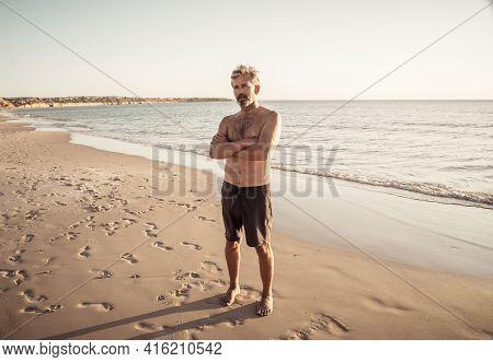 Mature Happy Active And Healthy Senior Adult Having Fun On The Beach Enjoying Retirement