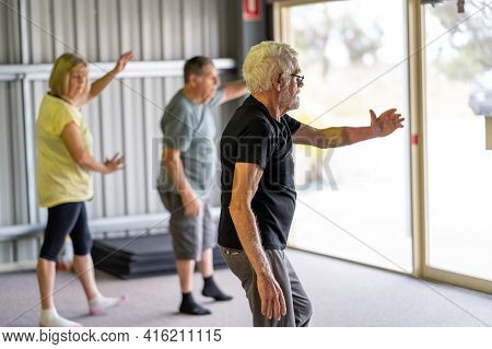 Group Of Elderly Senior People Practicing Tai Chi Class In Age Care Gym Facilities.