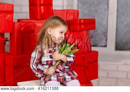 Smiling Kid Receiving A Surprise Gift For Her Birthday With Happy Expression. Funny Surprised Little