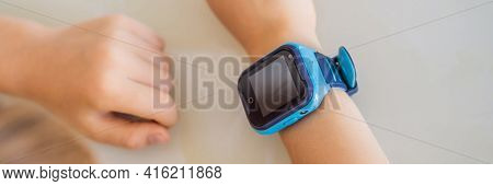 Banner, Long Format Little Boy Sitting At The Table And Looking Smart Watch. Smart Watch For Baby Sa