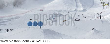 Panoramic View Of Snowpark With Figures For Freestyle Jumping And Jibbing In Ski Resort