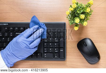Housewife Cleaning The House, Wipes Dust From Black Computer Keyboard With Blue Cleaning Rag. Househ