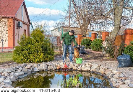 Mature Caucasian Man With His Dog Cleans A Garden Pond From Water Plants And Falling Leaves And Plac