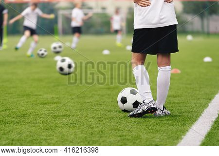 Soccer Players On Training Pitch. Group Of Footballers Kicking Soccer Balls On Practice Unit. Young