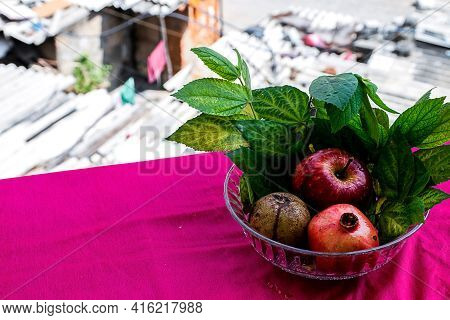 Stock Photo Of An Apple, Pomegranate And Sapodilla Fruit Kept In A Glass Bowl On Pink Background Dec
