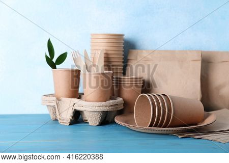 Set Of Disposable Eco Friendly Dishware On Light Blue Wooden Table