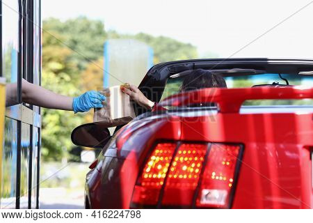 Woman In Car Receiving Order Of Food In Paper Bag